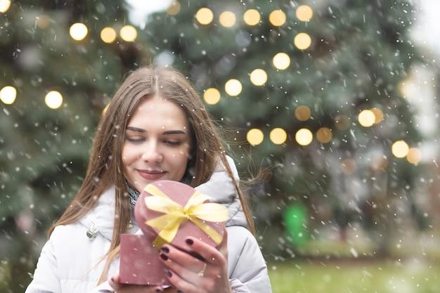Mujer rubia complacida sosteniendo una caja de regalo en la calle durante las nevadas. espacio vacio