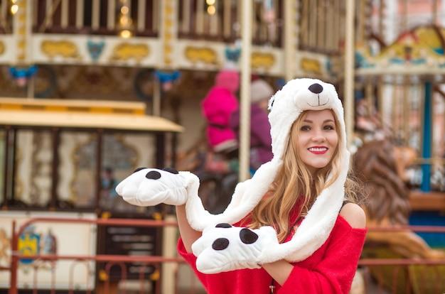 Mujer rubia complacida con suéter de punto rojo y sombrero divertido, posando en el fondo del carrusel con luces