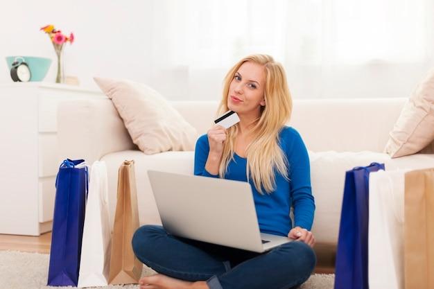 Mujer rubia con compras online y tarjeta de crédito