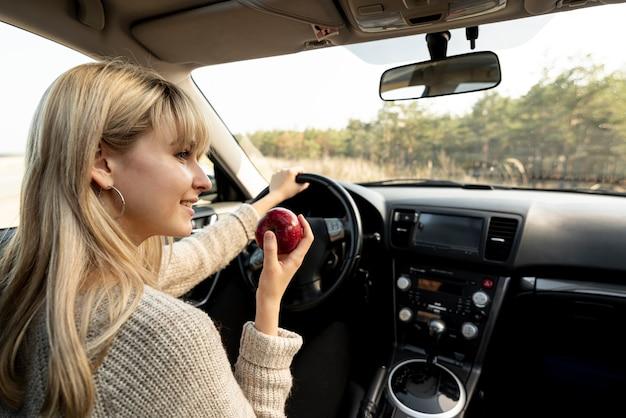 Mujer rubia conduciendo y comiendo una deliciosa manzana
