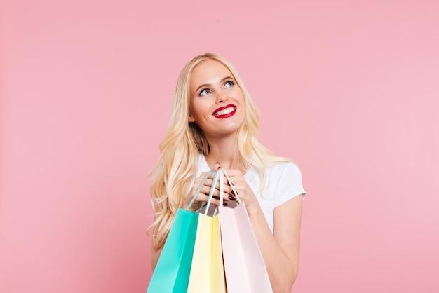 Mujer rubia contenta sosteniendo paquetes y mirando hacia arriba sobre rosa
