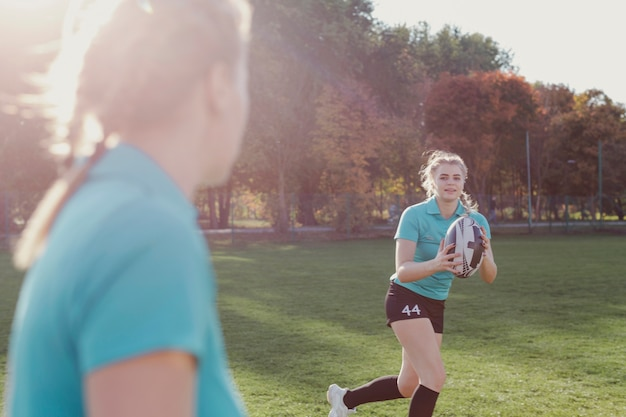 Mujer rubia corriendo con una pelota de rugby