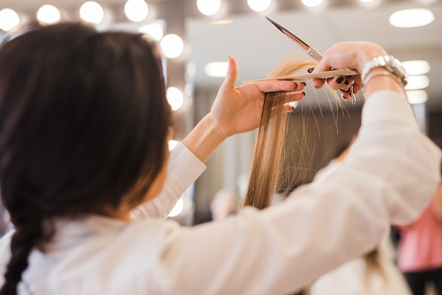 Mujer rubia cortándose el pelo