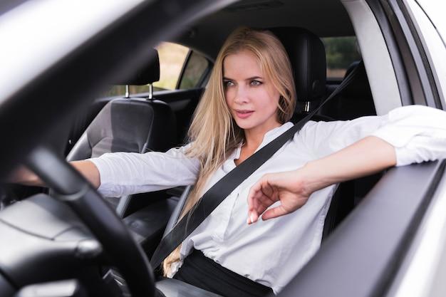 Mujer rubia cuidadosa conduciendo un automóvil