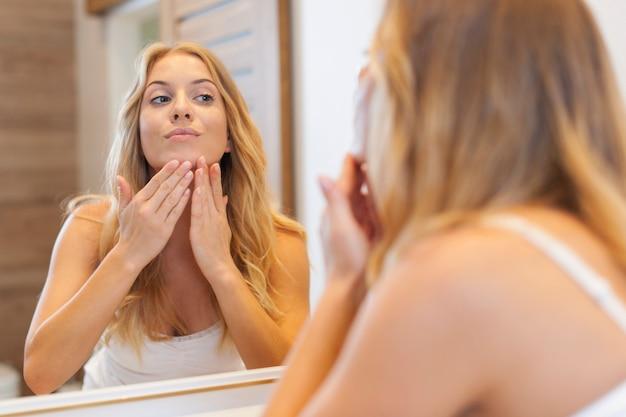 Mujer rubia cuidando de su piel en la cara