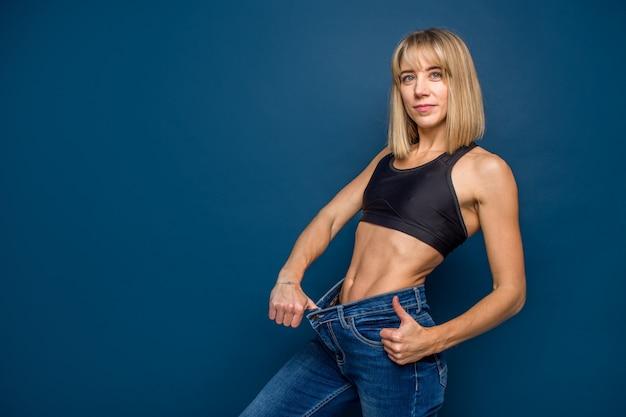 Mujer rubia delgada en jeans de gran tamaño sobre fondo azul, espacio para texto. pérdida de peso, fitnes, concepto de liposucción