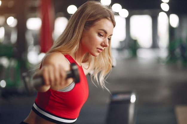 Mujer rubia deportiva en un entrenamiento de ropa deportiva en un gimnasio