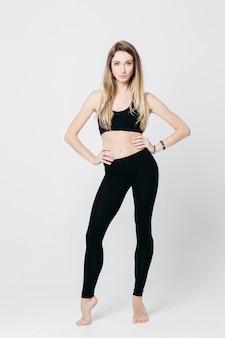 Mujer rubia deportiva en negro después de entrenar en el gimnasio.