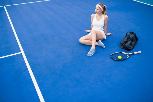 Mujer rubia descansando en la cancha de tenis