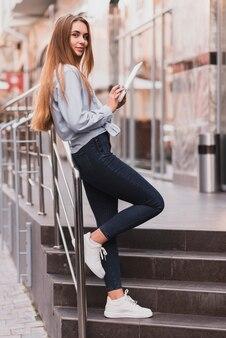 Mujer rubia descansando sobre la baranda y sosteniendo una tableta