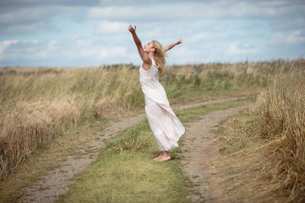 Mujer rubia despreocupada de pie en el camino del campo