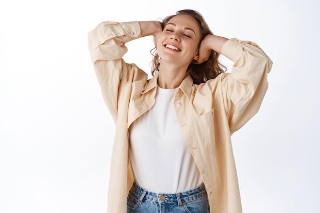 Mujer rubia despreocupada que se relaja, toca el cabello y se siente libre y feliz, cierra los ojos, disfruta del ocio, de pie contra la pared blanca