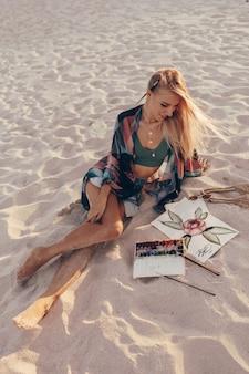 Mujer rubia dibujo acuarela flor con pincel en la playa