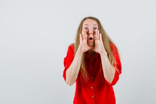 Mujer rubia diciendo secreto con las manos cerca de la boca en camisa roja,