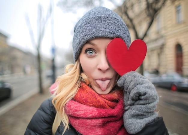 Mujer rubia divertida con un corazón de papel