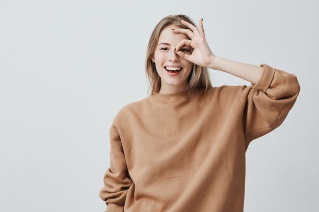 Mujer rubia divertida positiva en ropa casual muestra signo ok