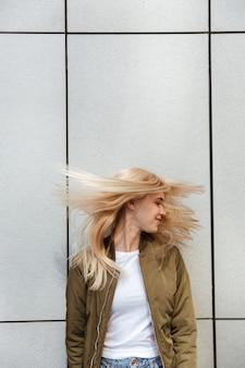 Mujer rubia divertida que sacude su pelo