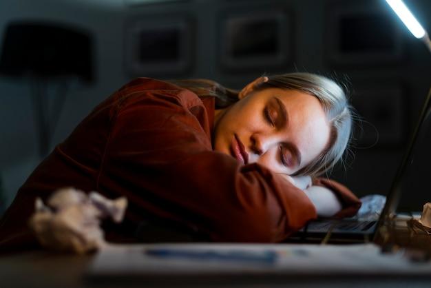 Mujer rubia durmiendo en la computadora portátil