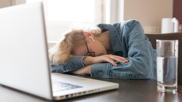 Mujer rubia durmiendo en la mesa de la cocina cerca del portátil
