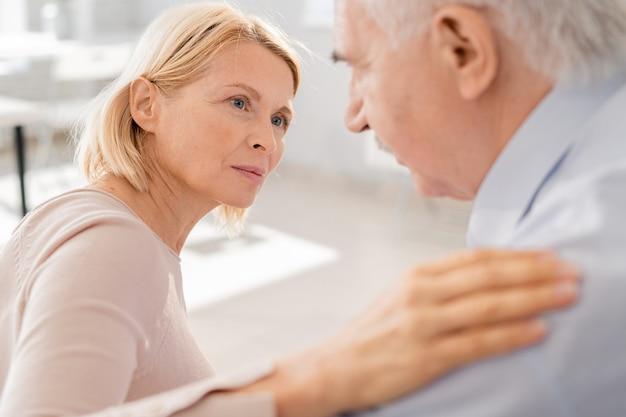 Mujer rubia envejecida compasiva mirando al hombre mayor que sufre mientras mantiene su mano sobre su hombro