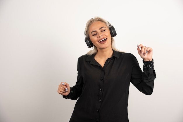 Mujer rubia escuchando la canción con auriculares sobre fondo blanco. foto de alta calidad
