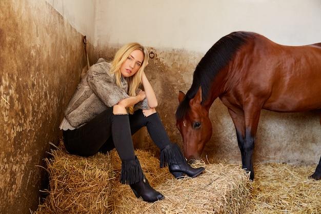 Mujer rubia en un establo interior con caballo