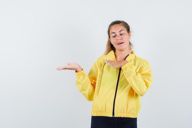 Mujer rubia estirando las manos como sosteniendo algo imaginario en chaqueta de bombardero amarilla y pantalón negro y mirando enfocado