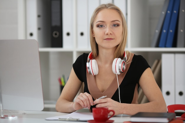 Mujer rubia estudia en línea, auriculares en el cuello, un bolígrafo en las manos