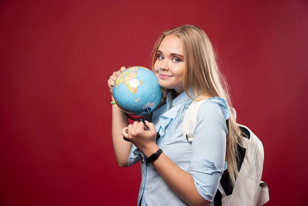 La mujer rubia estudiante sostiene un globo terráqueo y parece positiva.