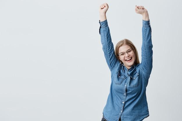 La mujer rubia feliz y contenta hace gestos de sorprenderse activamente al recibir un regalo inesperado de su novio, levanta los brazos en el aire, tiene una expresión emocionada. concepto de personas y emociones positivas.