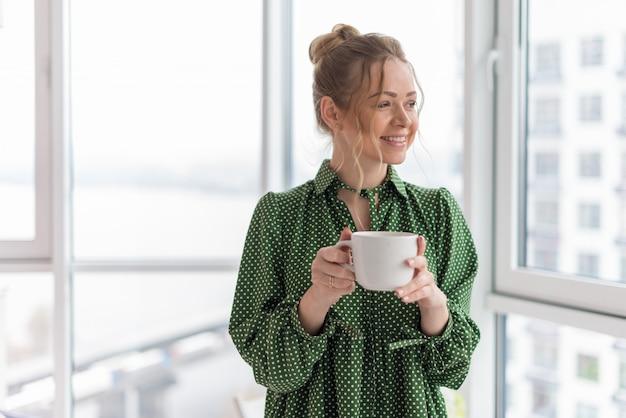 Mujer rubia feliz de la elegancia en un rascacielos que sostiene una taza