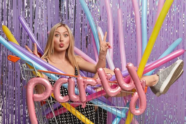 Mujer rubia en fiesta en carrito de compras con globos