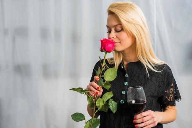 Mujer rubia con flor y copa de vino.