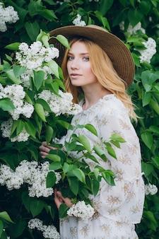 Mujer rubia con flores lilas en la primavera