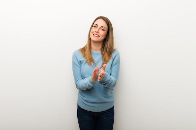 Mujer rubia en el fondo blanco aislado que aplaude después de la presentación en una conferencia