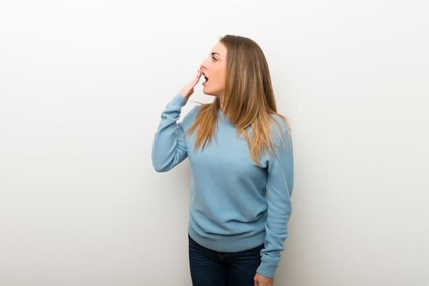 Mujer rubia en el fondo blanco aislado que bosteza y que cubre boca abierta con la mano