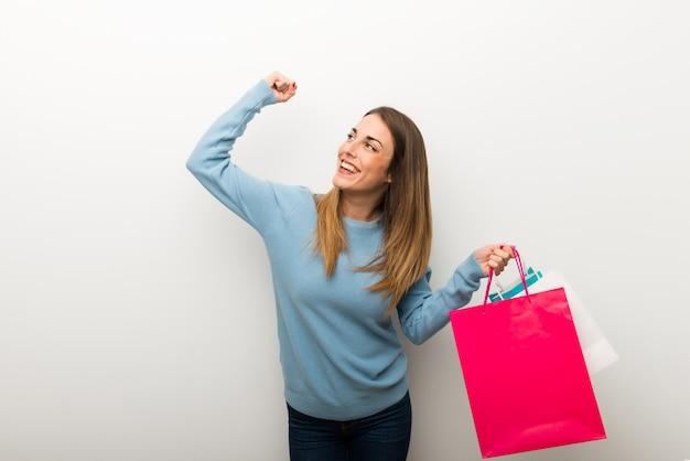 Mujer rubia en el fondo blanco aislado que sostiene muchos bolsos de compras en la posición de la victoria