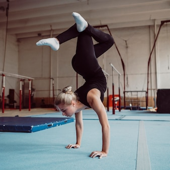 Mujer rubia formación para juegos olímpicos de gimnasia
