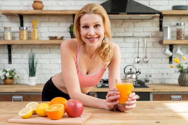 Mujer rubia con frutas en la cocina