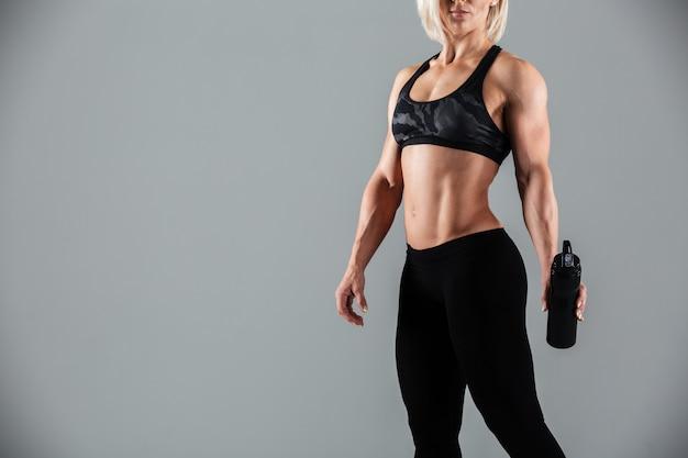 Mujer rubia fuerte deportes sosteniendo una botella de agua,