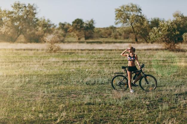 La mujer rubia fuerte con un traje colorido se sienta en una bicicleta en una zona desértica con árboles y pasto verde y mira el sol. concepto de fitness.