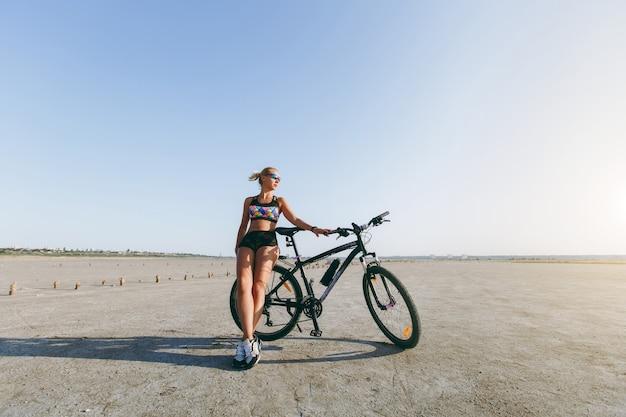 La mujer rubia fuerte con un traje multicolor y gafas de sol se encuentra cerca de una bicicleta en una zona desértica y mira al sol. concepto de fitness.