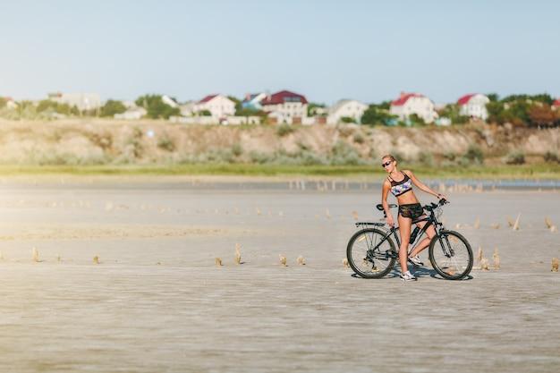 La mujer rubia fuerte con un traje multicolor y gafas de sol se sienta en una bicicleta en una zona desértica. concepto de fitness.
