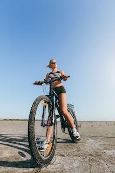La mujer rubia fuerte con un traje multicolor y gafas de sol se sienta en una bicicleta en una zona desértica y mira el sol. concepto de fitness.