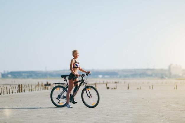 La mujer rubia fuerte con un traje multicolor se sienta en una bicicleta en una zona desértica y mira al sol. concepto de fitness.