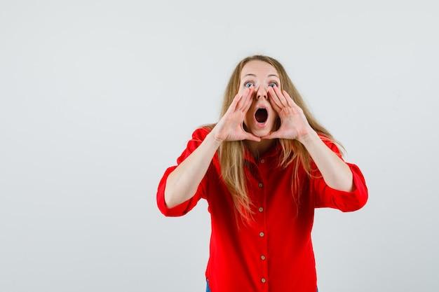 Mujer rubia gritando o diciendo un secreto en camisa roja y mirando emocionado,