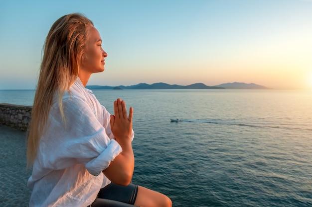 Mujer rubia haciendo ejercicio de respiración pranayama en puesta de sol sobre el mar. .