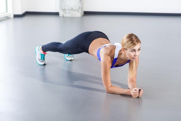 Mujer rubia haciendo push up o plancha. foto de estudio, aislado sobre fondo gris