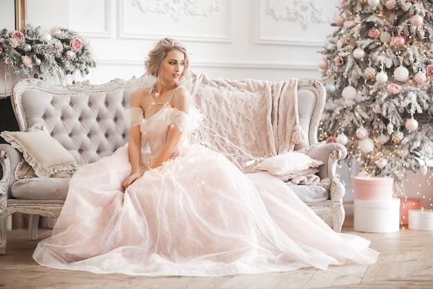 Mujer rubia hermosa joven en altura completa de la escena de la navidad. señora atractiva en vestido rosa precioso.