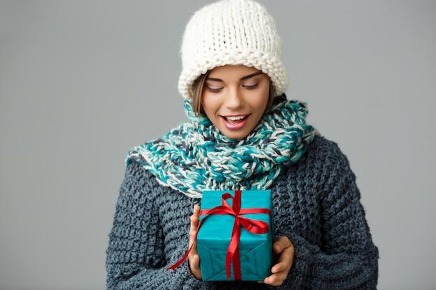 Mujer rubia hermosa joven en suéter hecho punto sombrero y bufanda que sonríe sosteniendo la caja de regalo en gris.